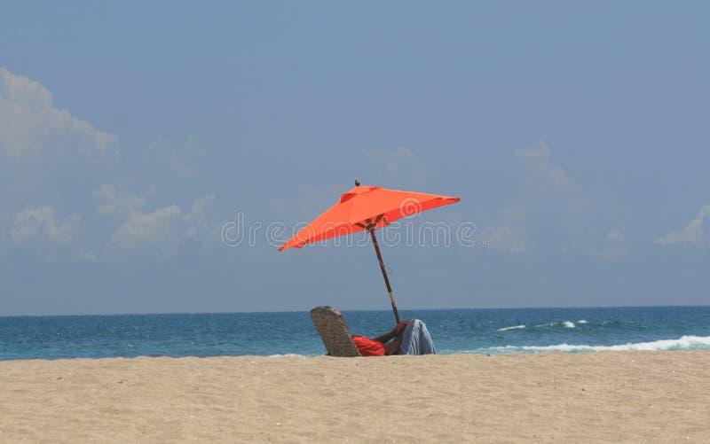 Persona sola sulla spiaggia sotto l'ombrello fotografie stock