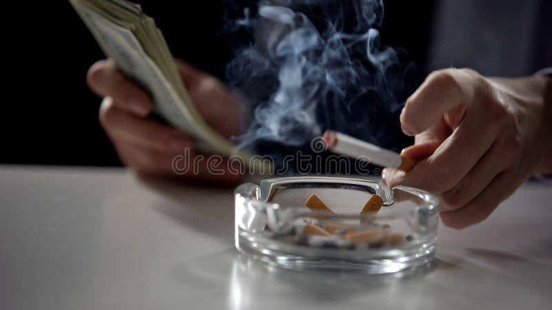 Persona in vestito che conta soldi e che fuma sigaretta, affare illegale di affari immagine stock libera da diritti