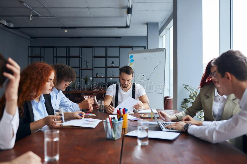 Group of caucasian young designers meeting Around Table In Modern Office royalty free stock photos