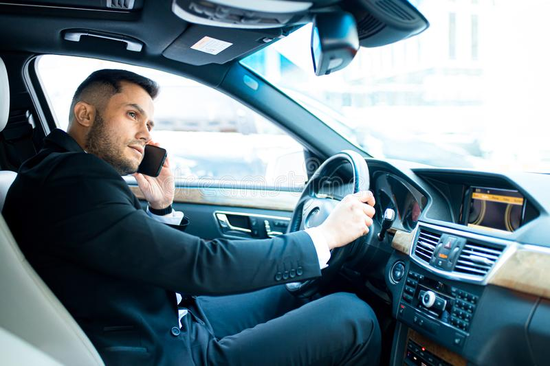 Successful man talk on phone with his business colleague while riding in car stock images