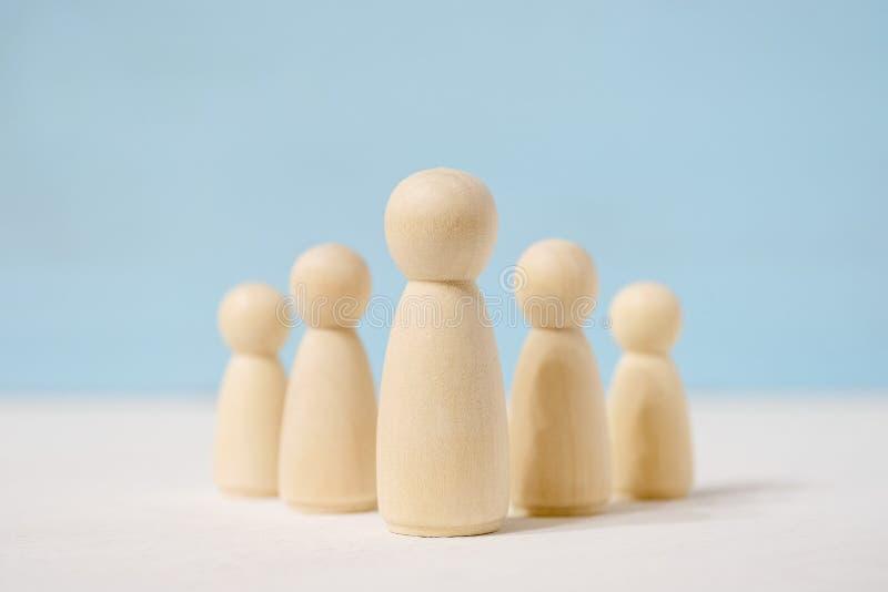 Personagens abstratos de brinquedo de madeira de chefe no centro e subordinados atrás dele imagens de stock