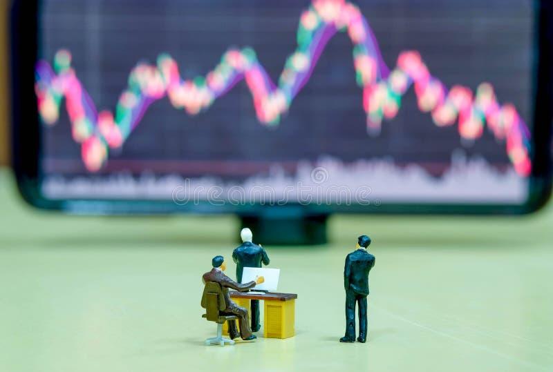 Personajes de negocios de figuras en miniatura o el bursátil mirando la junta de valores de Blur para el análisis gráfico foto de archivo libre de regalías