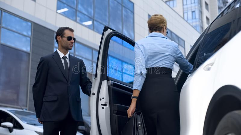 Personal assistant of female politician opening car door to his boss, service stock image