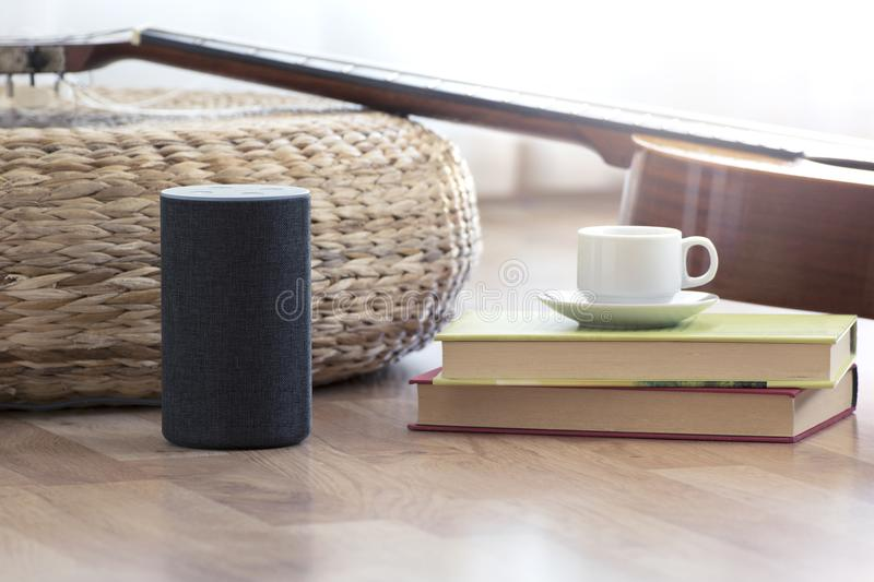Personal assistant loudspeaker on a wooden floor of a smart home living room. Next, a guitar and some books and a cup of coffee. royalty free stock images