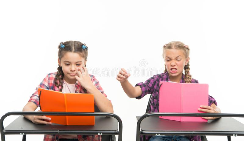 Personal attitude determines success. Acquiring knowledge. Small girls with books sit at desks reading lesson. Little. Children learn reading and writing at stock image