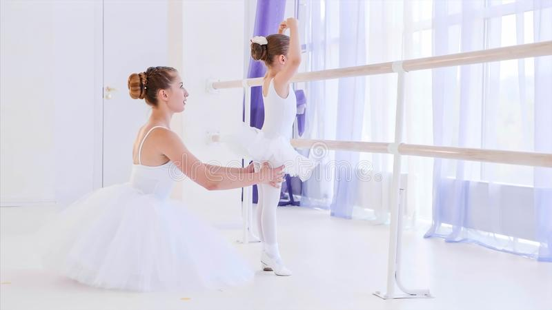 Ballet teacher is teaching little girl near the barre stand. royalty free stock photo