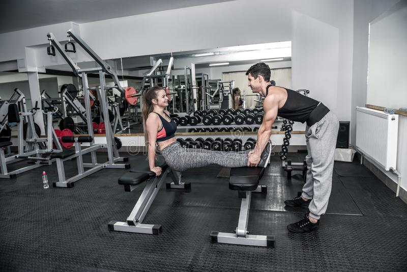 Personal coach helping to young woman in gym royalty free stock images