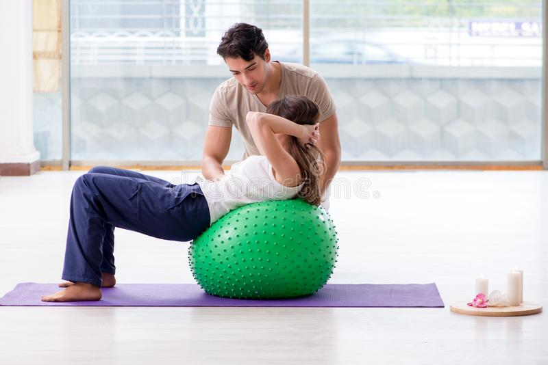 The personal coach helping woman in gym with stability ball royalty free stock image