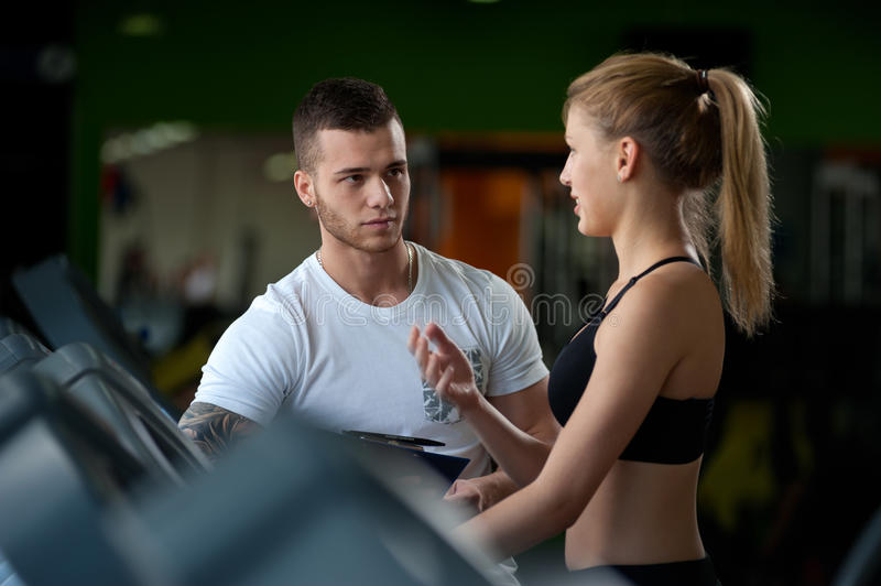 Personal coach talking with female client in gym stock image