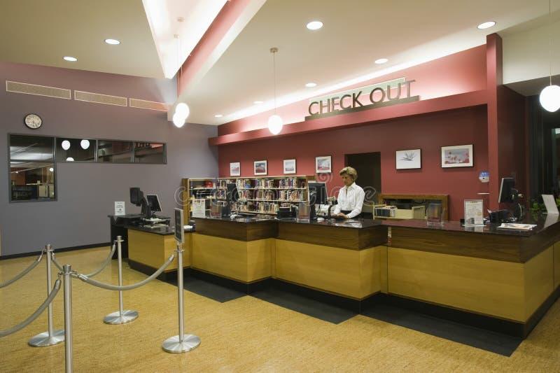 Personal de biblioteca en el contador de pago y envío foto de archivo libre de regalías