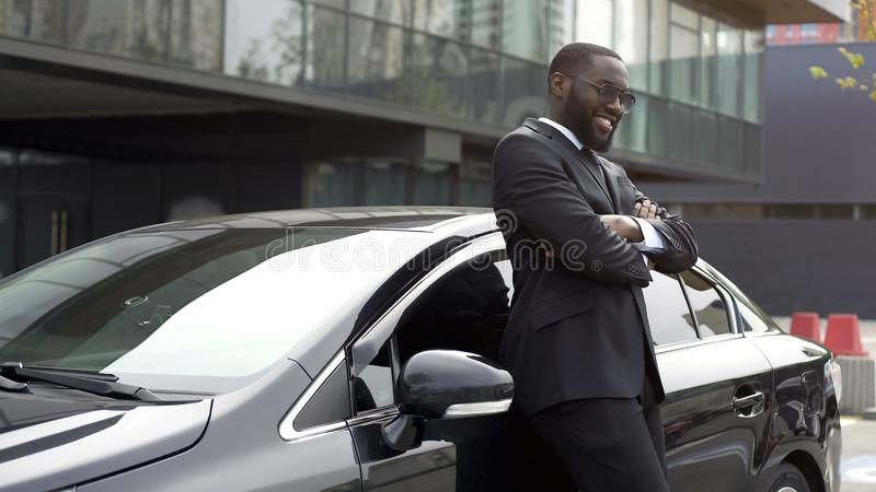 Personal driver of important person on chic car, loving and enjoying his work. Stock photo royalty free stock photos