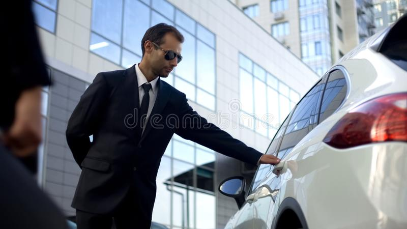 Personal driver meeting and opening car door for lady boss, bodyguard duties stock photos