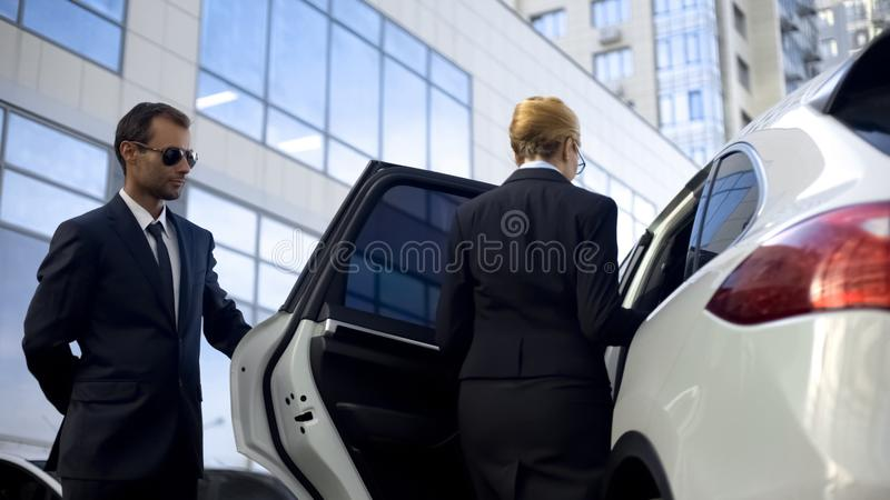 Personal driver waiting for boss on parking lot, helping her to get into car stock images