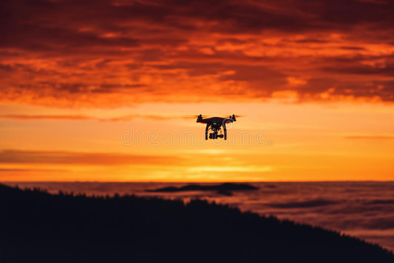 Personal drone flying through the air at sunset stock photos