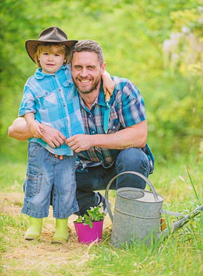 Personal example. Little helper in garden. Planting flowers. Growing plants. Take care of plants. Boy and father in royalty free stock photos