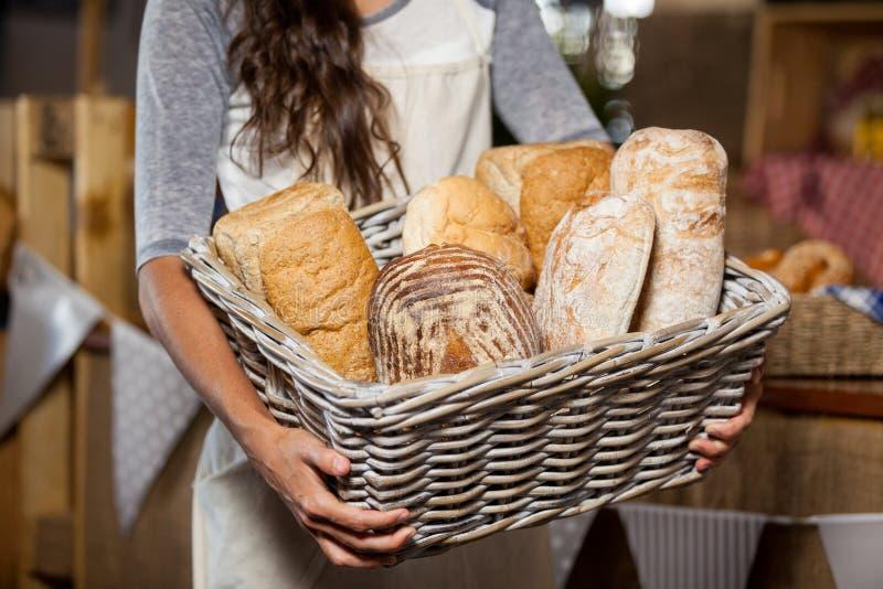 Personal femenino que sostiene la cesta de mimbre de diversos panes en el contador en tienda de la panadería imagen de archivo