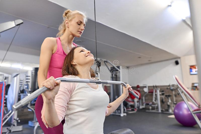 Personal fitness instructor helping summer woman exercising in health club. Health fitness sport age concept stock image