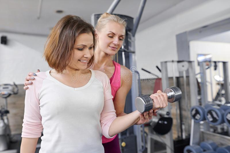 Personal fitness instructor helping summer woman exercising in health club. Health fitness sport age concept royalty free stock images