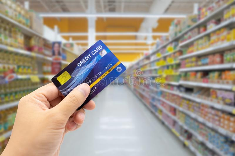 Personal hand holding credit card, with Abstract blurred supermarket view of empty supermarket aisle, defocused blurry background royalty free stock photos
