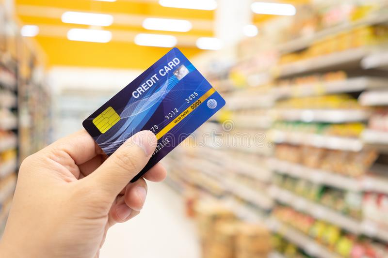 Personal hand holding credit card, with Abstract blurred supermarket view of empty supermarket aisle, defocused blurry background stock photo