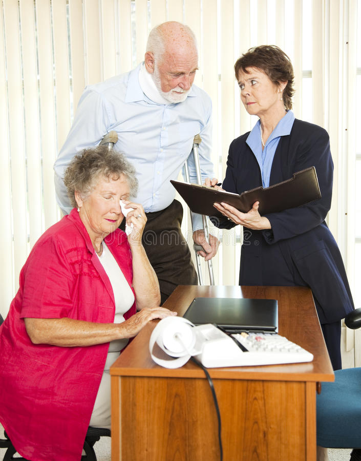 Personal Injury Attorney. Injured senior man and his upset wife meet with a personal injury lawyer stock photography