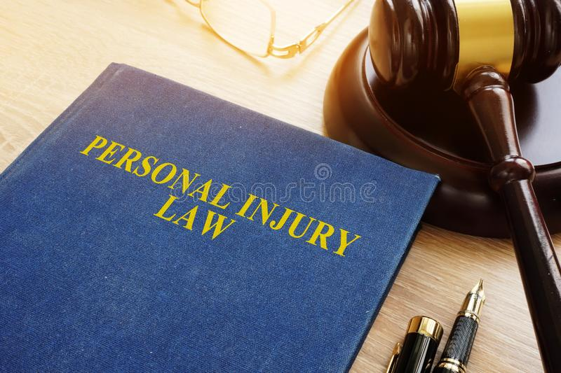 Personal injury law on a desk and gavel. Personal injury law on a desk and gavel on a desk royalty free stock image