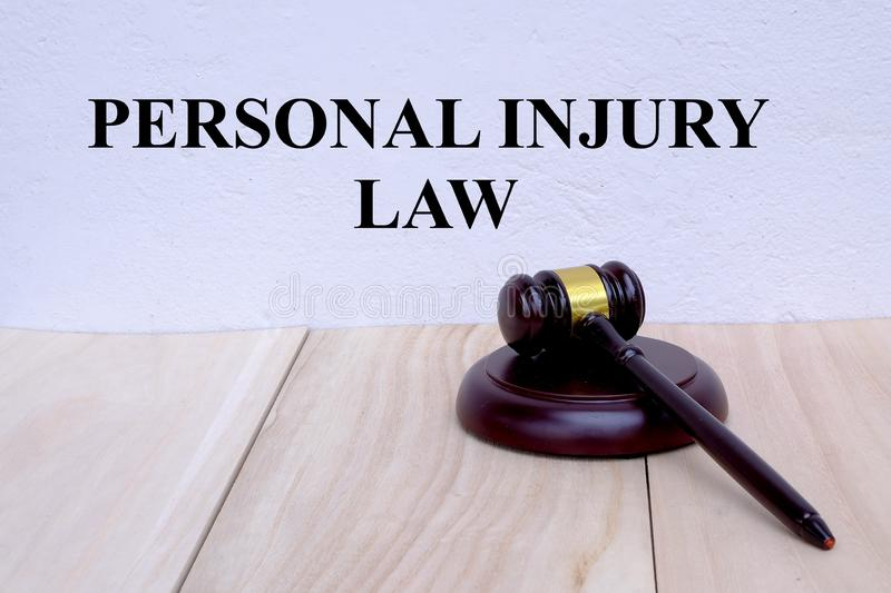 Personal Injury Law written on the wall with gavel on wooden background. Law concept.  royalty free stock image