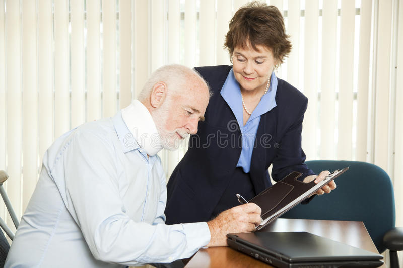 Personal Injury Lawyer with Client. Personal injury lawyer signs up a new injured client stock image