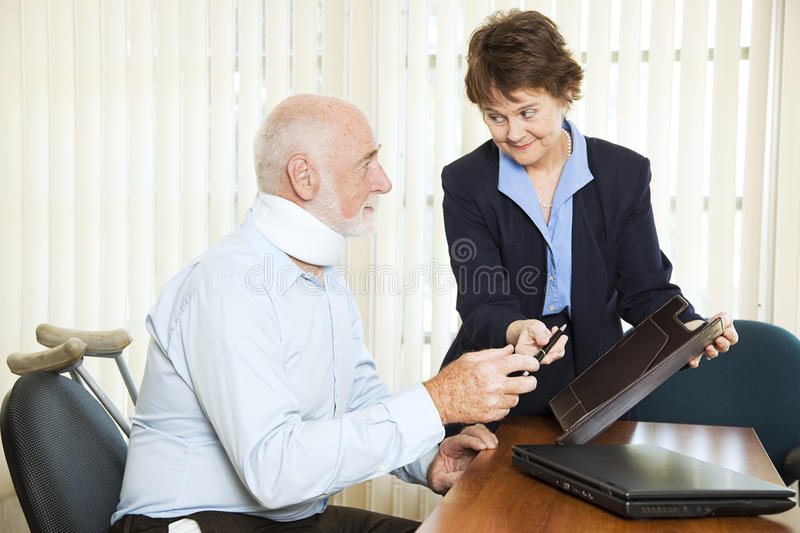 Personal Injury Settlement. Injured man signing a settlement offer from the attorney royalty free stock image