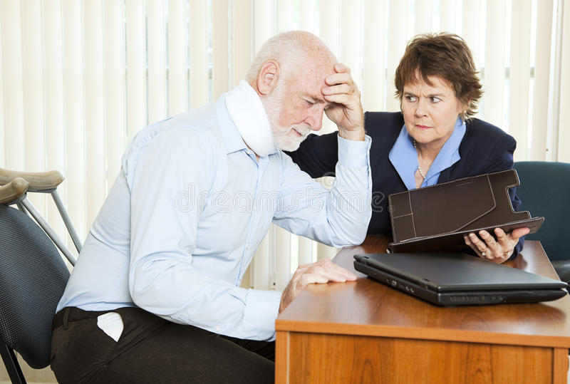 Personal Injury Suffering. Injured man in pain, discussing a lawsuit with his attorney royalty free stock photography