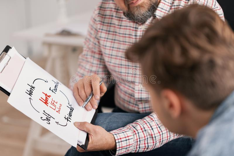 Personal life coach explaining graph to his young patient stock photography