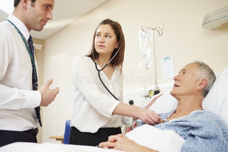 Personal médico en rondas que examina al paciente masculino mayor imagenes de archivo