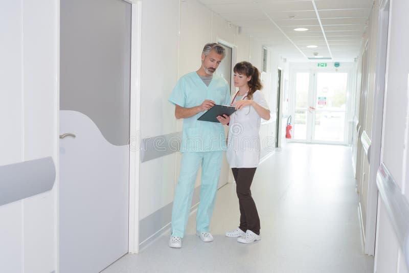 Personal médico que mira el tablero en pasillo del hospital imagen de archivo libre de regalías