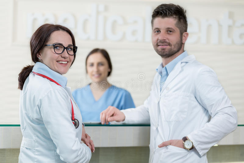 Personal médico que tiene discusión en pasillo moderno del hospital imagen de archivo