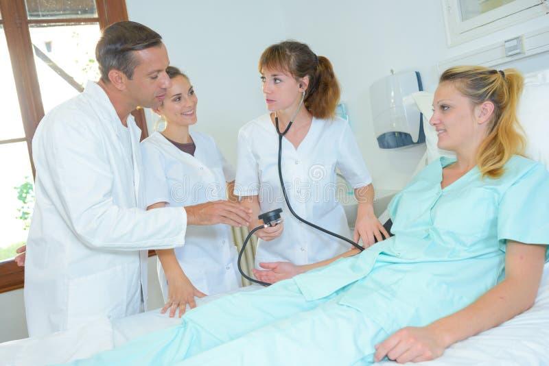 Personal médico que toma a ` paciente s la presión arterial imágenes de archivo libres de regalías