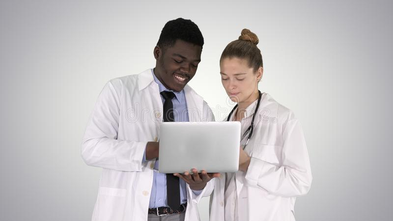 Personal médico que trabaja delante de un ordenador portátil gris mientras que se coloca en fondo de la pendiente fotos de archivo