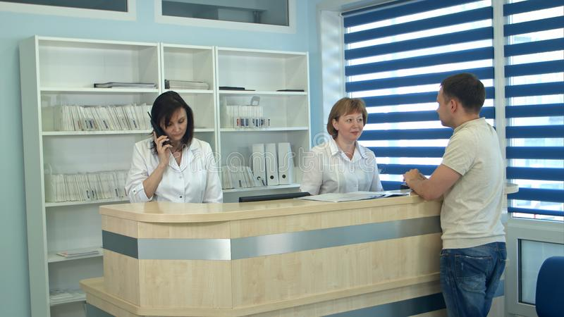Personal médico que trabaja en el mostrador de recepción médico ocupado fotografía de archivo libre de regalías