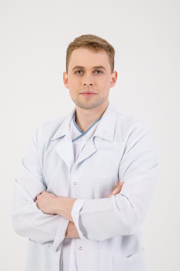 Personal m?dico El doctor comprensivo joven se coloca aislado en un fondo blanco vestido en un uniforme para los doctores imágenes de archivo libres de regalías