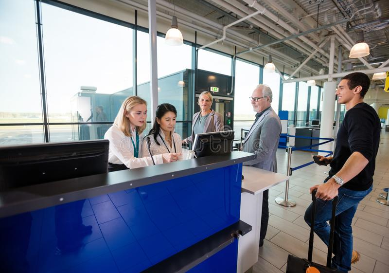 Personal que usa el ordenador mientras que pasajeros que esperan en aeropuerto fotografía de archivo