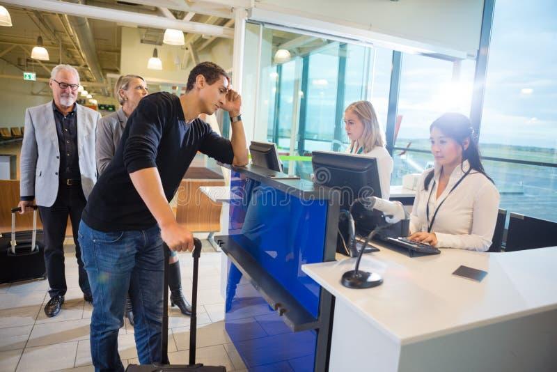 Personal que usa los ordenadores mientras que pasajeros que esperan en el aeropuerto fotos de archivo
