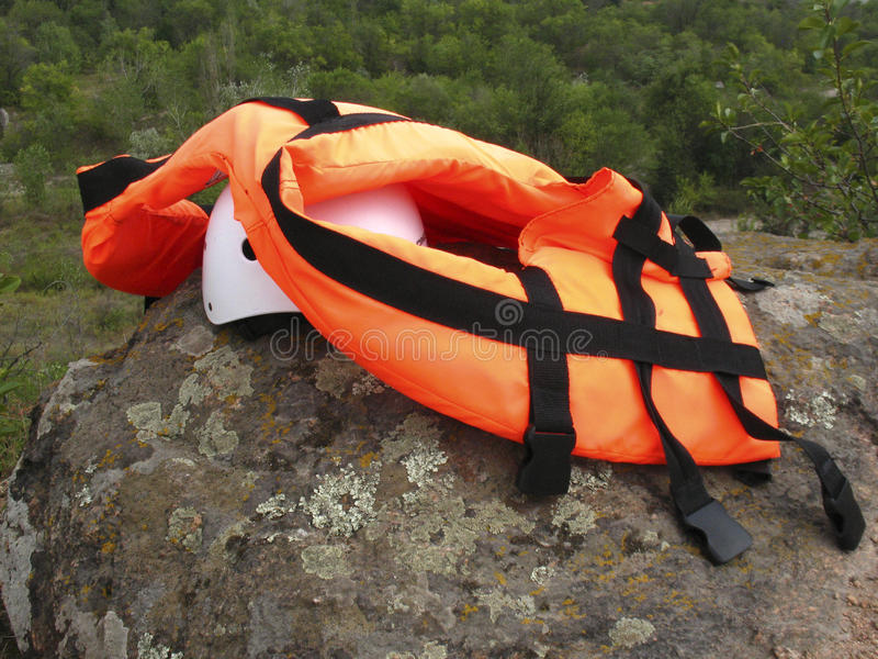 Personal safety equipment. Life jacket and helmet lying on the big stone stock photo