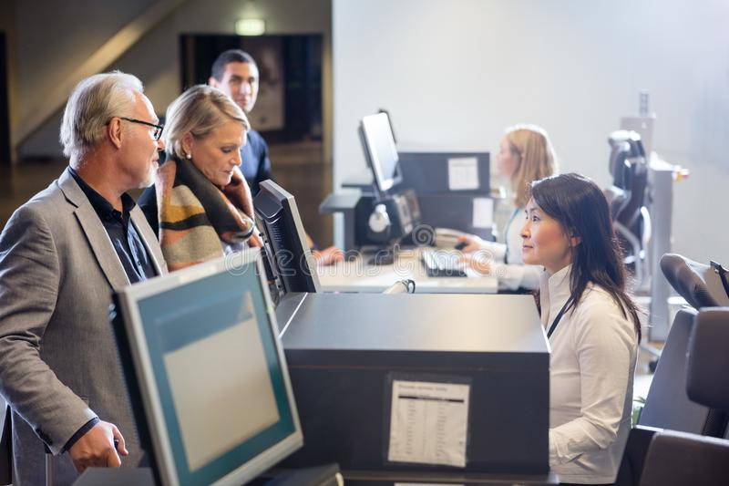 Personal som ser höga affärspar på flygplatsincheckningskrivbordet royaltyfri bild