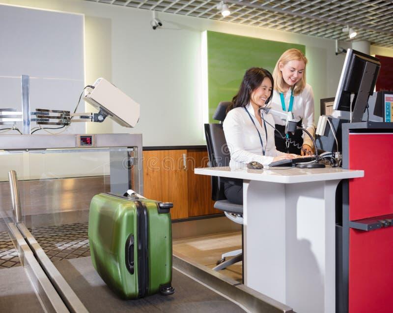 Personal som väger bagage på flygplatsincheckningskrivbordet arkivbild
