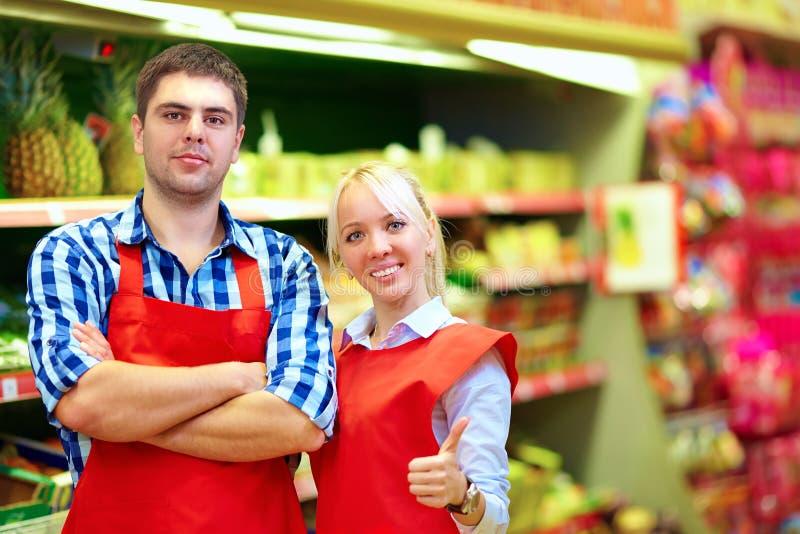 Personal sonriente del ultramarinos que trabaja en supermercado foto de archivo