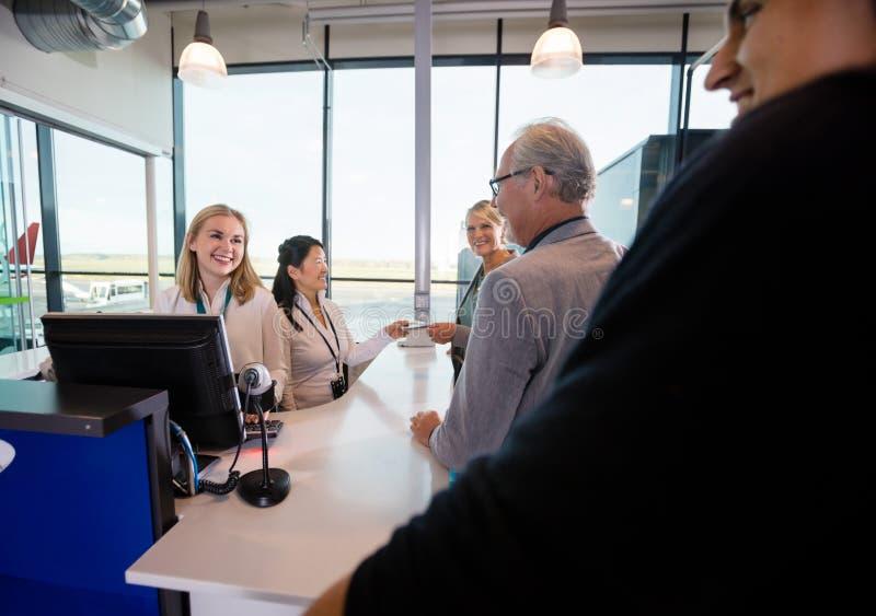 Personal sonriente que mira a pasajeros el contador en aeropuerto foto de archivo