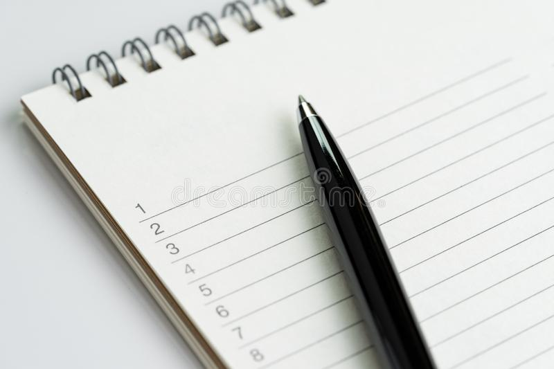 Personal to do lists or new year`s resolution concept by closed. Up of list of numbers on white clean notepad with pen on it royalty free stock photo