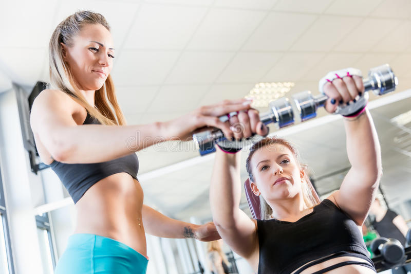 Personal trainer assistance during fatburning exercise. stock image