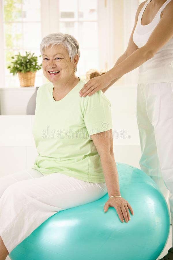 Personal trainer assisting senior woman stock photo