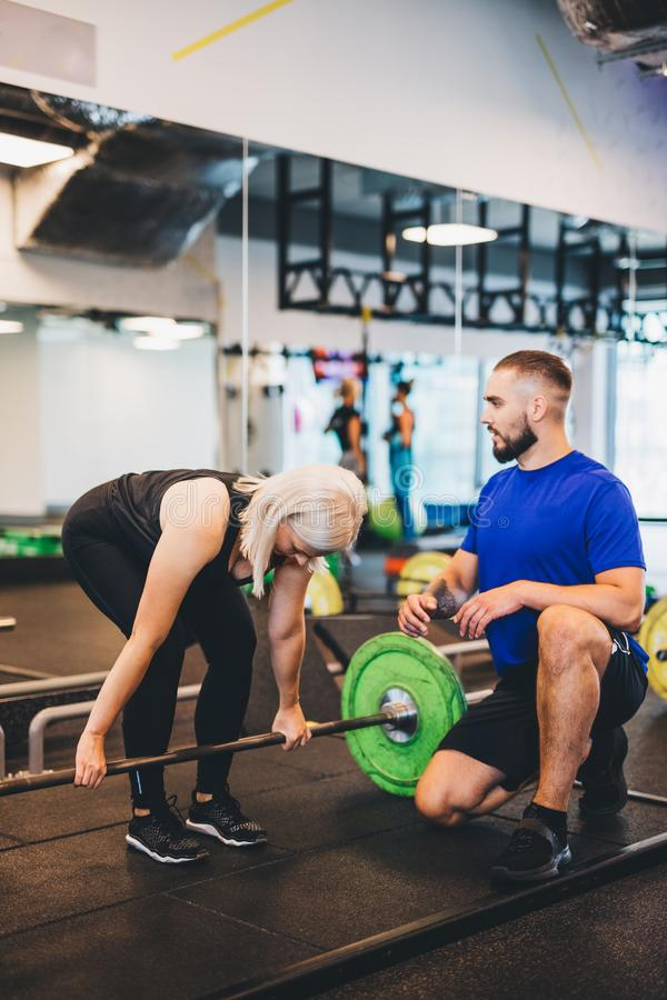 Personal trainer assisting woman lifting weights. stock photos