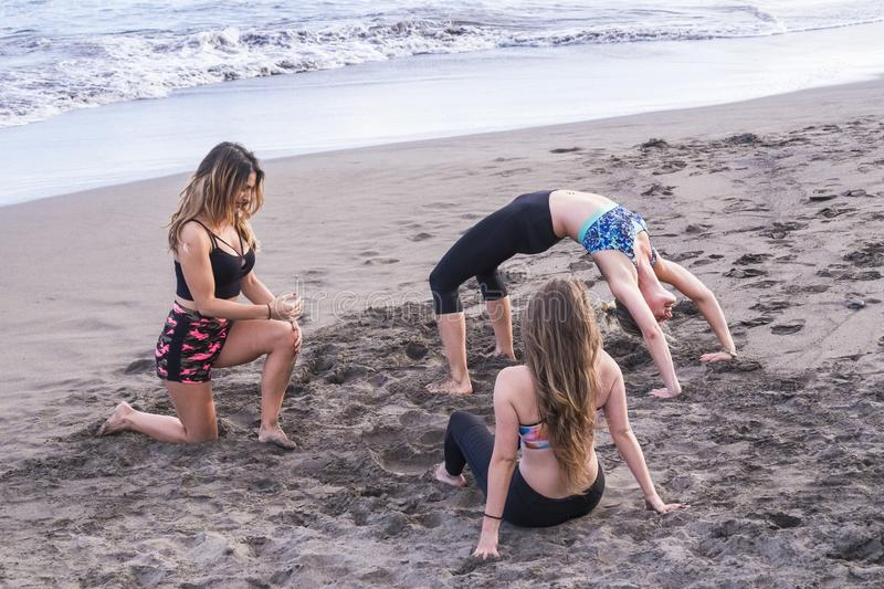 Personal trainer and class of pilates at the outdoor beach with three beautiful young girls enjoying the sport active exercises royalty free stock image